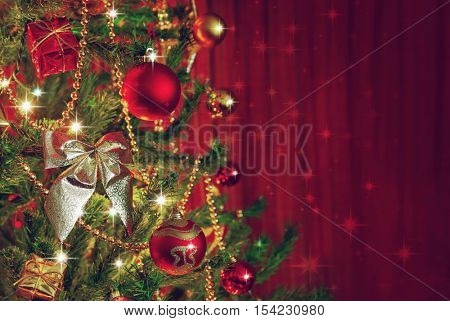 Detail of a Christmas tree next to red window curtains with copy space