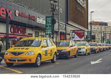 Bucharest Romania - April 22 2014: Yellow taxi cabs wait in line for customers in front of Unirea Shopping Center a large shopping complex in Union Square with a total area of 83971 square meters.