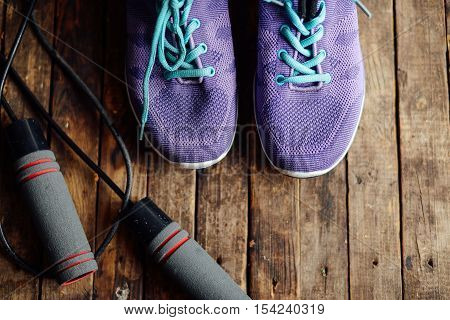 set for sports on wooden table closeup. Rope and sneakers on the dark wooden background. Shoe on wooden background. Sport clothes and accessories on a wooden background View from above