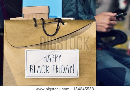 a young caucasian man sitting in a street bench using his smartphone with some gifts and a shopping bag in the foreground with the text happy black friday written in it