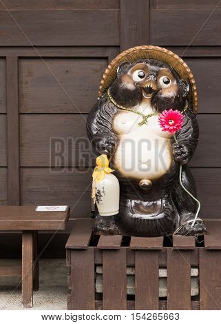 Takayama Japan - September 24 2016: The legendary Tanuki statue holds red flower and the customary Sake flask. On brown wooden stand and brown background.