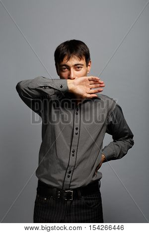 Young asian brunet man in grey shirt standing at grey background with negation or covering gesture