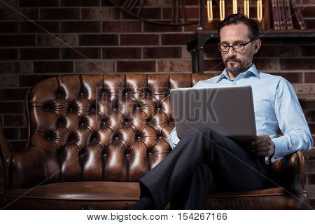 Using technology. Serious hard working self employed man sitting on the sofa and holding a laptop on his knees while working on it