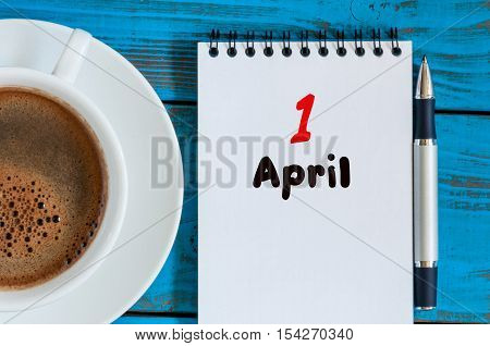 April 1st. Day 1 of month, calendar with morning coffee cup, at workplace. Spring time, Top view.