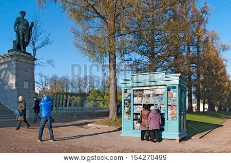 TSARSKOYE SELO, SAINT - PETERSBURG, RUSSIA - OCTOBER 19, 2016: People near pavilion choose souvenirs with views of The State Museum Preserve and take pictures of Flora Statue of The Cameron Gallery