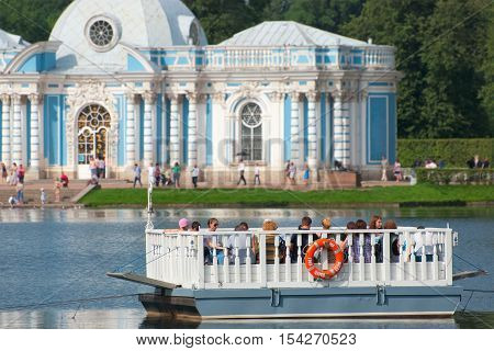 TSARSKOYE SELO, SAINT - PETERSBURG, RUSSIA - JULY 25, 2016: People on the ferry on The Great Pond in front of The Grotto Pavilion. The ferry connects The Admiralty with the Hall on the Island