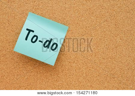 A reminder to do your tasks Bulletin board with a blue sticky note with text To-do
