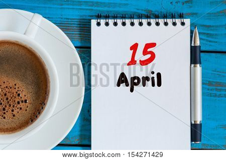 April 15th. Day 15 of month, calendar with morning coffee cup, at workplace. Spring time, Top view.