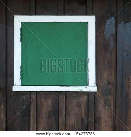 A closed square window with green shutters