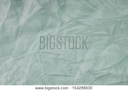 Green wrinkled drapery fabric texture background. Close up