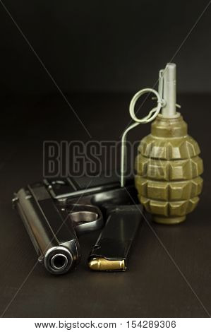 Pistol and a grenade on the table. Preparing for battle. Handgun with ammunition on a dark wooden table. Sales of weapons and ammunition. Advertising on ammunition. New gun and ammunition.