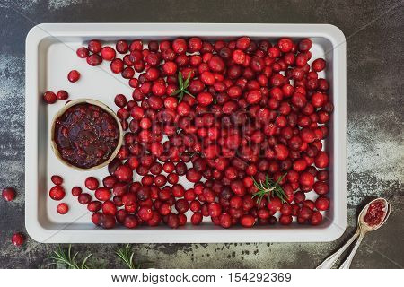 Cranberry jam and fresh cranberries on a baking tray. Top view, blank space, rustic surface