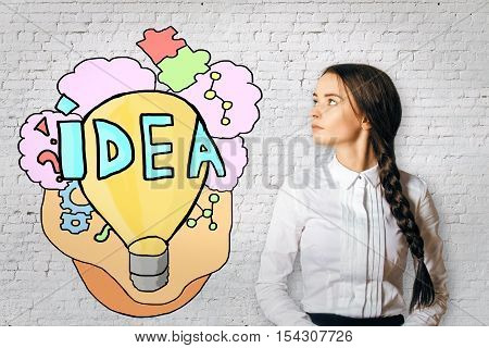 Side portrait of attractive young female and creative lamp drawing on white brick wall background. Idea concept