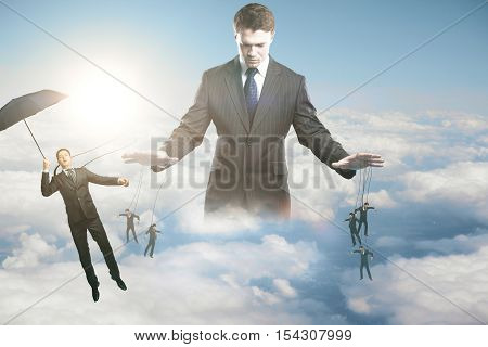 Pensive young businessman manipulating subordinates on sky background with sunlight. Control concept