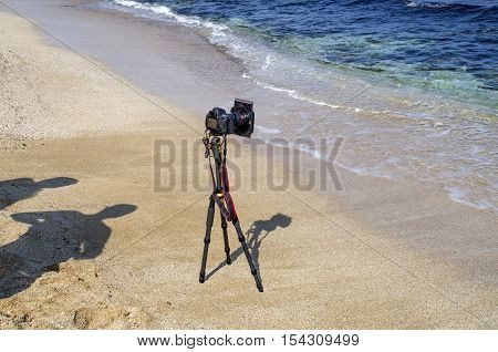 Camera on tripod at the beach and shadow of two photographers