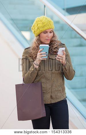 woman shopping with coffee and mobile or cell phone
