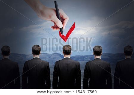 Hand choosing best candidate by ticking him with red checkmark. HR and choice concept