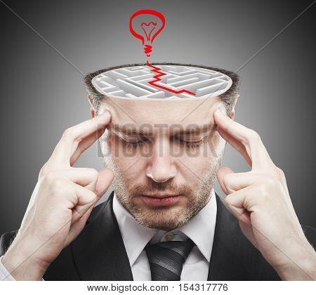 Thoughtful young businessman with abstract concrete maze and red lamp sketch inside head. Brainstorming ideas concept