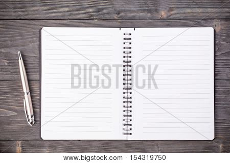 Office supply ballpen with notepad on gray wooden table