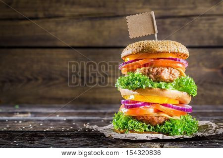 Tasty and big double-decker burger on wooden table