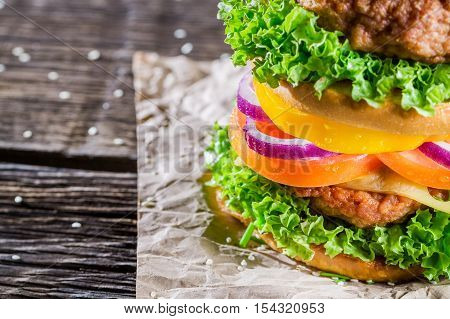 Homemade double-decker burger with vegetables on wooden table
