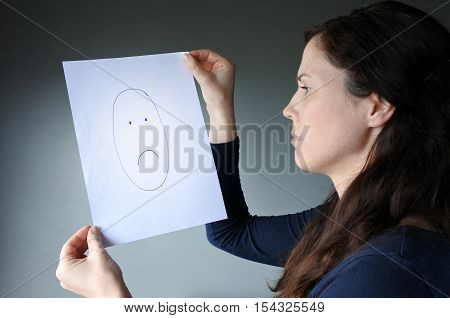 Young Woman Looks At A Drawing With A Sad Face