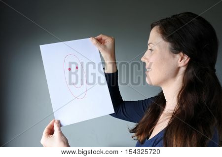 Young Woman Looks At A Drawing With A Happy Face