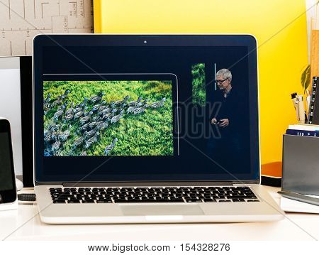 PARIS FRANCE - OCT 28 2016: Apple Computers website on new MacBook Pro Retina with OLED Touch bar in geek creative room showcasing Apple Keynote Tim Cook talking about the MacBook Pro and its advantages