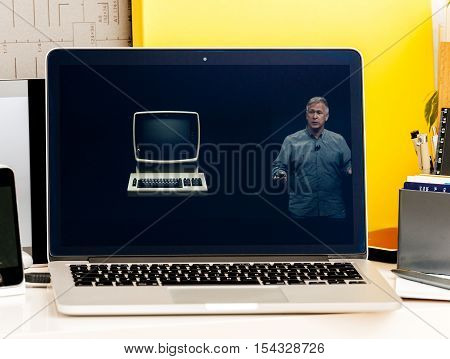PARIS FRANCE - OCT 28 2016: Apple Computers website on new MacBook Pro Retina with OLED Touch bar in geek creative room showcasing Apple Keynote Philip Schiller talking about old IBM PC