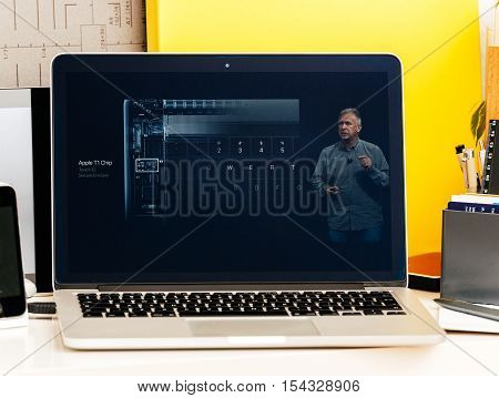 PARIS FRANCE - OCT 28 2016: Apple Computers website on new MacBook Pro Retina with OLED Touch bar in geek creative room showcasing Apple Keynote presentation of Apple T1 Chip - secure cryptographic engine for Touch ID