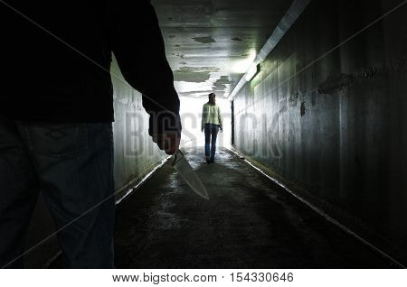 Man Carries A Knife Follows A Young Woman In A Dark Tunnel