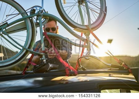 man checking straps on bike rack with selective focus and lens flare