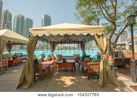DUBAI, UAE - OCTOBER 11, 2016: The recreation and pool area of the Palace Hotel in Dubai overlooking skyscrapers in the background including Burj Khalifa and The Address Hotel