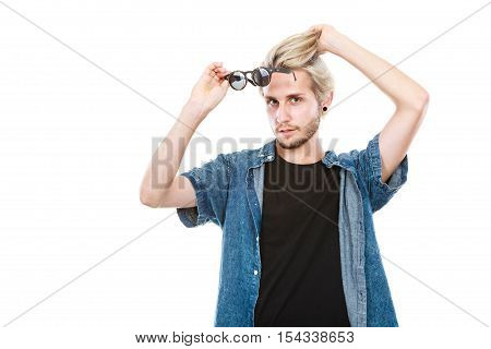 Men fashion modeling concept. Hipster man wearing jeans outfit showing eccentric glasses studio shot isolated