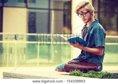 Hipster Guy Holding Notebook Sitting On Ledge