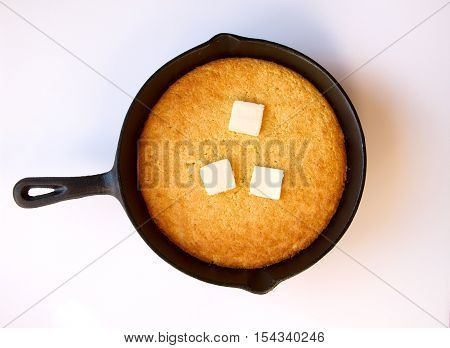 Butter melting on hot cornbread that was cooked in a black cast iron skillett isolated on white