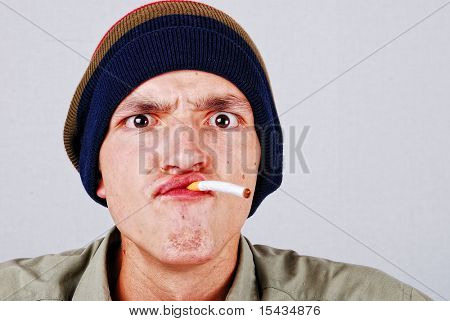 Funny face young man with cigarette in hand