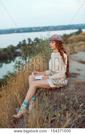 Woman writer concept. Student thinking and writing notes. Joyful happy girl sitting writing and reading outdoors on the nature.