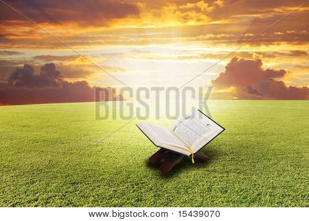 Holy book Koran, opened on the meadow with light shining from inside