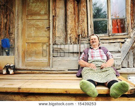 ältere Frau vor ihrem alten Haus
