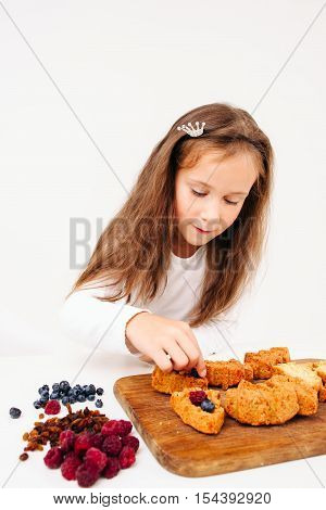 Girl preparing sweet cakes with berries. Young lassie cooking at kitchen. Christmas pastry homemade baking.