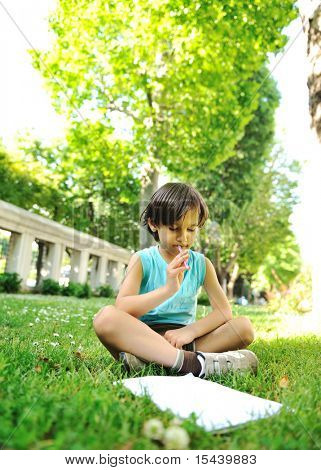 Kid writing and drawing in park