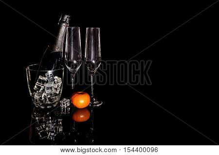 Bottle of champagne in an ice bucket with two wineglasses and mandarin