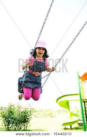 On the playground, swinging