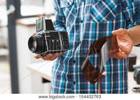 Photographer standing with retro camera and negative film. Unrecognizable man holding old fashioned photographing equipment. Electronic development, technology evolution, hobby concept
