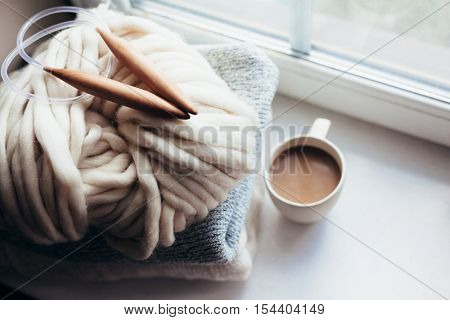 Stack of cozy knitted sweaters, thick yarn and wooden needles on window sill. Chunky knit. Morning coffee in lazy winter weekend.