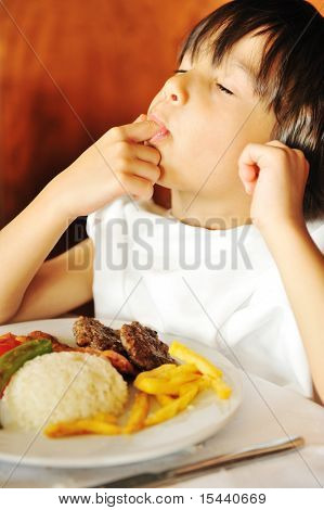 Real enjoying food, cute kid with finger in his mouth