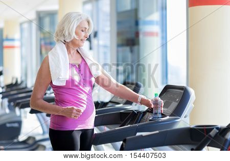 Better than yesterday. Pretty positive senior woman smiling and taking bottle of water while having a rest after running on treadmill.