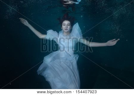 Woman in white dress underwater dancing around splashes of water.
