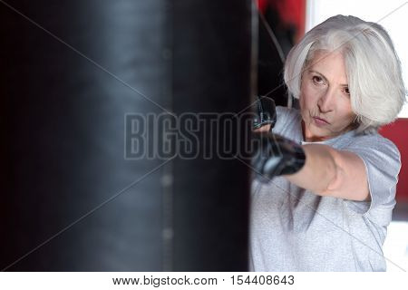My passion is box. Enthusiastic senior pretty woman boxing punching bag while training in a gym.